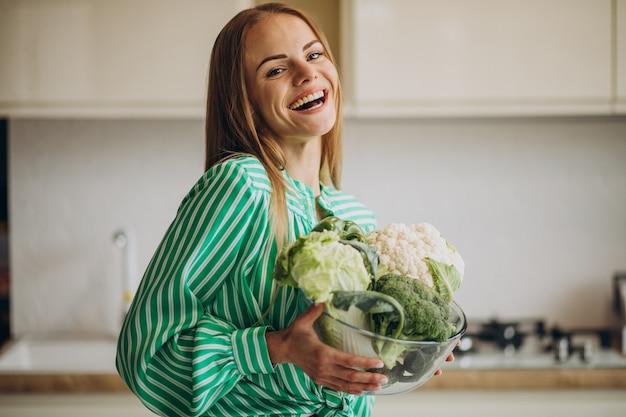 Молодая женщина улыбается и держит цветную капусту Бесплатные Фотографии