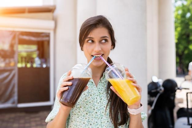 Giovane donna sorridente e beve due cocktail con ghiaccio in bicchieri di plastica con paglia sulla strada cittadina. Foto Gratuite