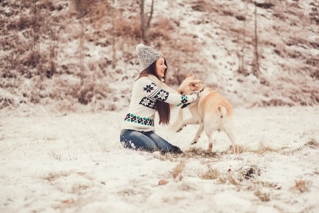 Young woman smiling and playing with the dog Premium Photo