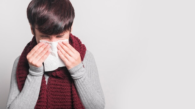 Young woman sneezing in tissue against gray background Free Photo