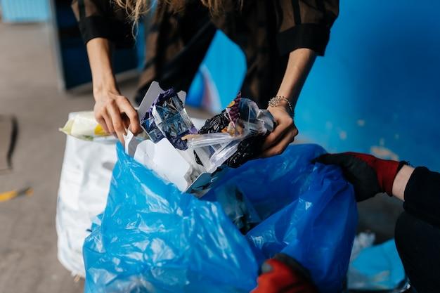 若い女性がゴミを分別します。リサイクルの概念。廃棄物ゼロ 無料写真