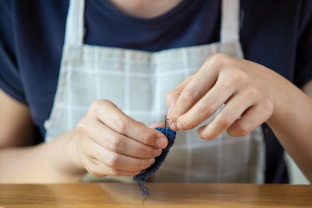 手作りの趣味で自由時間を過ごす若い女性。自宅での滞在中にかぎ針編みの帽子とバッグを作る熟練した女性。インスピレーションと創造性は、コピースペースとコンセプトを動作します。 Premium写真