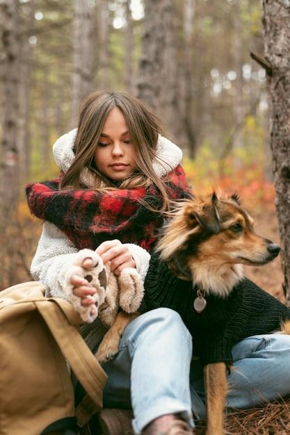 Giovane donna che trascorre del tempo insieme al suo cane in una foresta Foto Gratuite