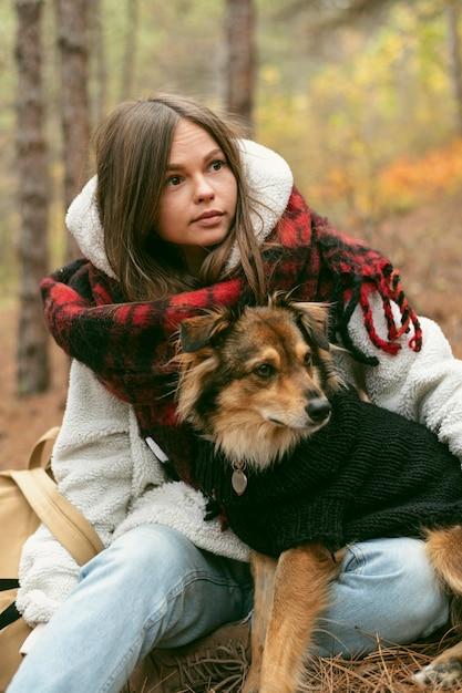 Giovane donna che trascorre del tempo insieme al suo cane all'aperto Foto Gratuite