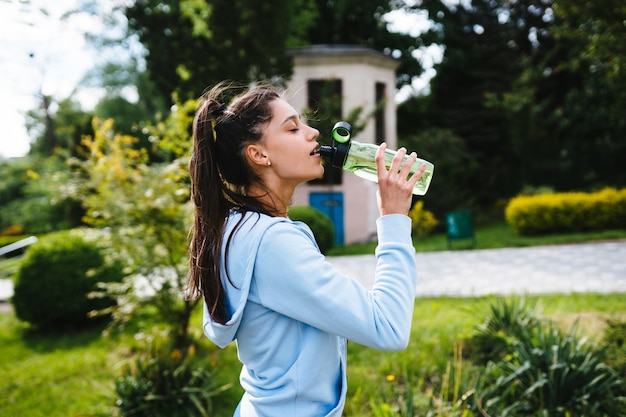 Young woman in a sporting suit drinks water from a bottle after outdoor gymnastics in the summer Free Photo