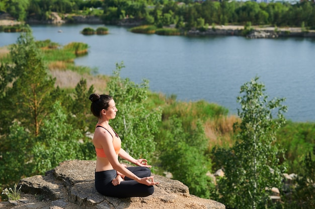Young woman in sports clothing sitting in lotus position and doing breathing exercise outdoors Premium Photo