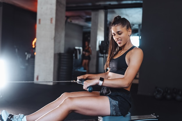 Young woman in sportswear in the gym, training and pulling weights in seated cable row machine. Free Photo