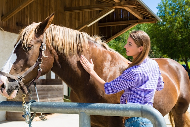 Young woman in the stable with horse Premium Photo