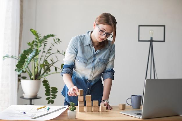 オフィスの仕事机の上の若い女性スタッキング木製ブロック 無料写真