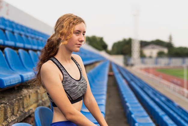 Young woman at stadium sitting Free Photo