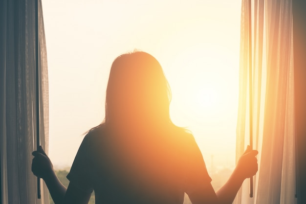 Young woman stand in the bedroom open curtain see sunrise after wake up Premium Photo