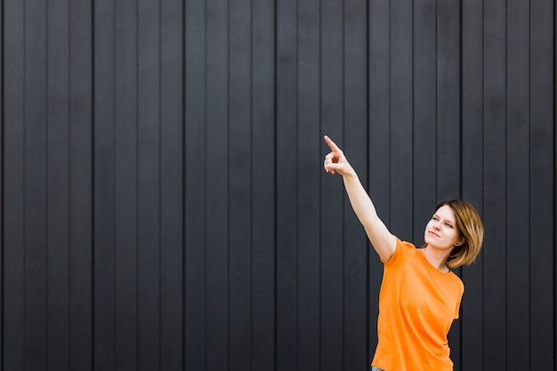 Young woman standing against black wall pointing her finger upward Free Photo