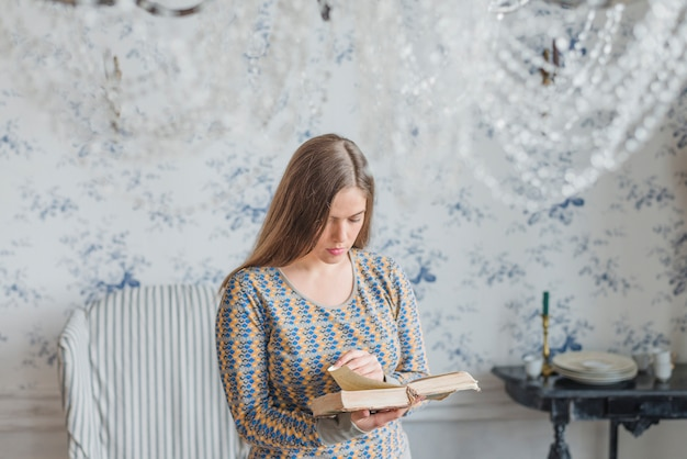 Young Woman Standing Against Wallpaper Reading Book Photo