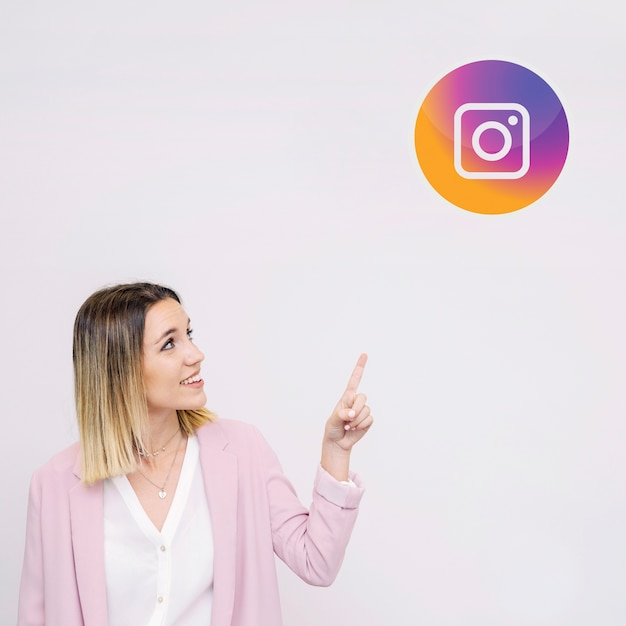 Young woman standing against white background pointing at instagram logo Free Photo
