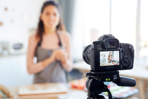 Young woman standing alone in her kitchen shooting bakery tutorial for her food blog channel Premium Photo