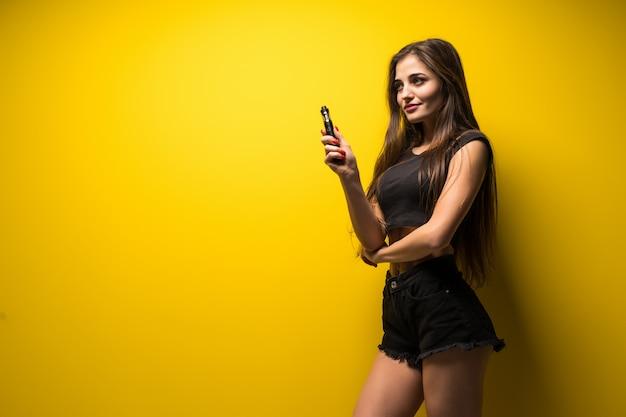 若い女性が立っていると黄色の壁にvaping。 無料写真