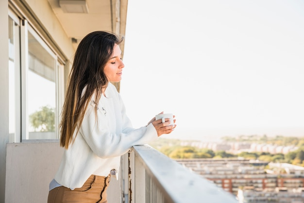 Young woman standing in balcony holding cup of coffee Free Photo
