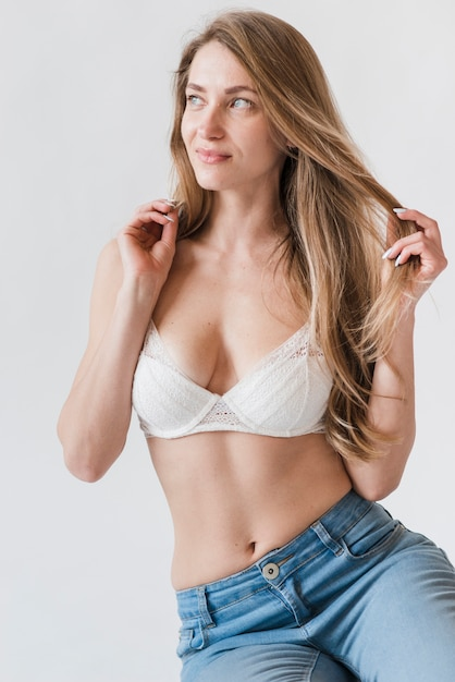 Young woman standing in bra and jeans Free Photo