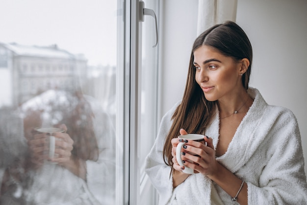 Young woman standing by the window drinking hot coffee Free Photo