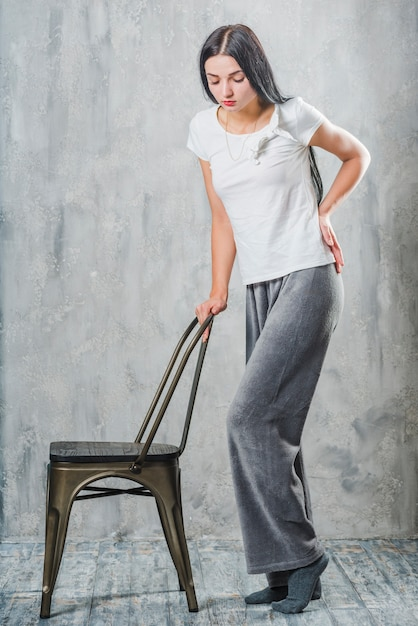 Young woman standing behind the chair having back pain Free Photo