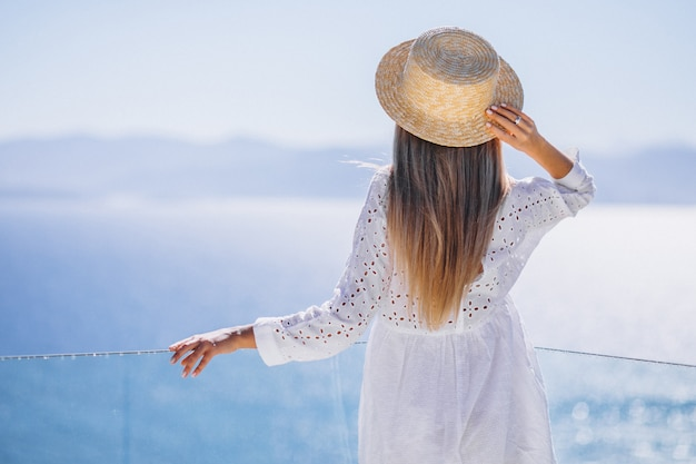 Young woman standing from the back and looking at the sea Free Photo