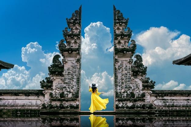 Молодая женщина стоит у ворот храма лемпуянг лухур на бали, индонезия. винтажный тон Бесплатные Фотографии