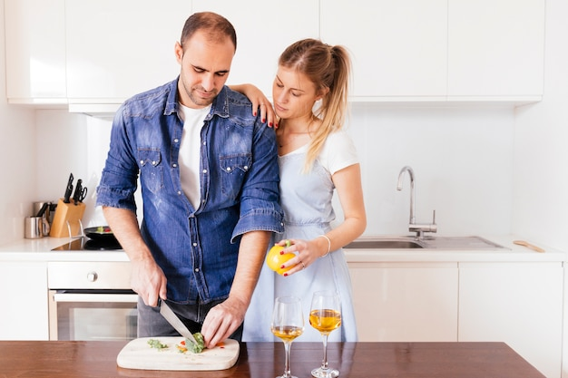 Young woman standing behind the man cutting the bellpepper with knife on table Free Photo