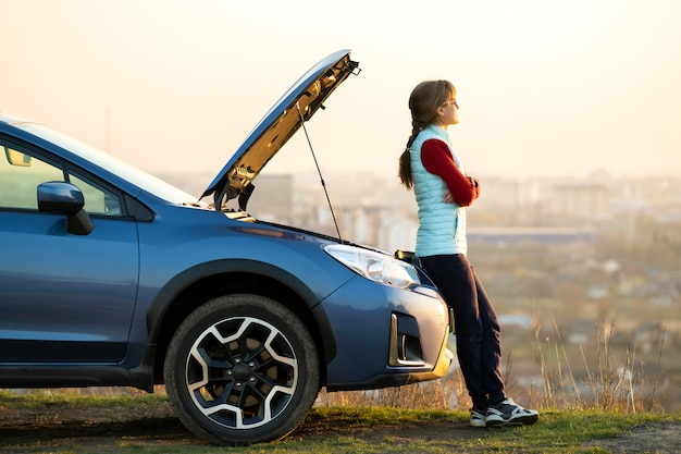 Молодая женщина, стоящая возле сломанного автомобиля с выскочил капот, возникли проблемы с ее транспортного средства. женщина водитель ждет помощи рядом с неисправностью авто. Premium Фотографии
