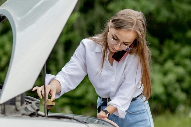 Молодая женщина, стоящая возле разбитой машины с поднятым капотом, испытывает проблемы с ее транспортным средством. жду помощи эвакуатора или техподдержки. женщина звонит в сервисный центр. Premium Фотографии