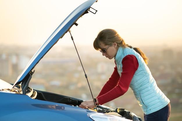 Молодая женщина, стоящая возле разбитой машины с поднятым капотом, испытывает проблемы с ее транспортным средством. Premium Фотографии
