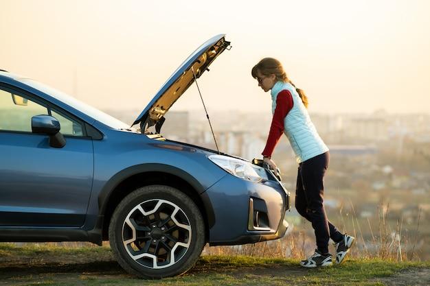 Молодая женщина, стоящая возле сломанной машине с выскочил капот, возникли проблемы с ее транспортного средства. Premium Фотографии