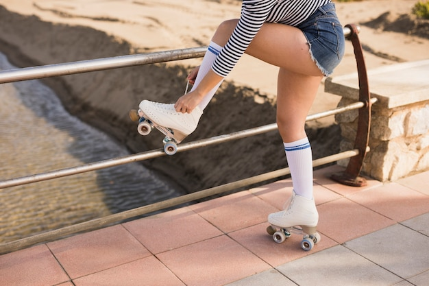Young woman standing near the railing tying lace on roller skate Free Photo
