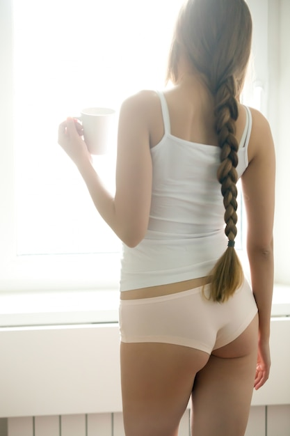 Young woman standing near the window drinking coffee Free Photo