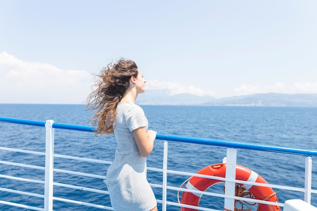 Young woman standing next to the ship's handrail looking at the blue sea Free Photo