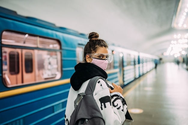 Young woman standing at station in medical protective mask Free Photo