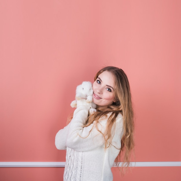Young woman standing with cute rabbit Free Photo