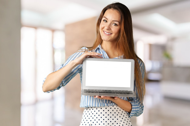 Young woman standing with laptop laptop in her hands Premium Photo