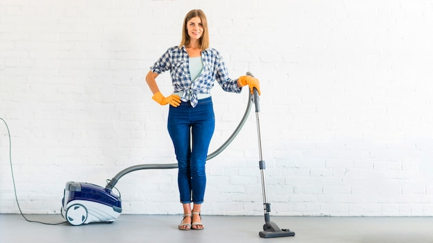 Young woman standing with vacuum cleaner in front of brick wall Premium Photo