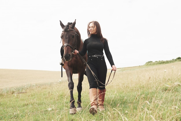 A young woman stands near her mount. she loves the animals and joyfully spends her time in their environment Premium Photo