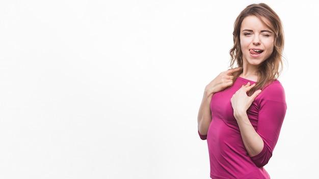 Giovane donna che attacca la sua lingua fuori posa su sfondo bianco Foto Gratuite