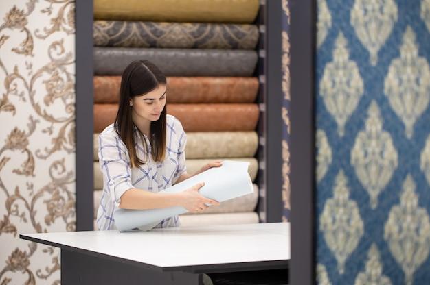 Una giovane donna in un negozio sceglie wallpaper per la sua casa. c Foto Gratuite