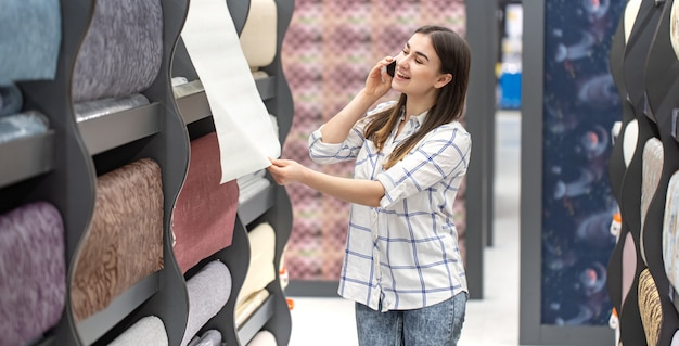 Una giovane donna in un negozio sceglie wallpaper per la sua casa Foto Gratuite