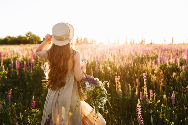 Young woman in straw hat and dress with bouquet of lupine flowers Free Photo