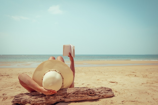 Young woman in straw hat lying sunbathe on a tropical beach, relax with book. Premium Photo
