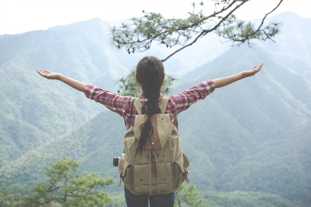 The young woman stretched both arms to the top of the hill in a tropical forest along with backpacks in the forest. adventure,hiking. Free Photo