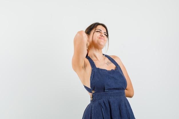 ドレスを着て腕を伸ばし、リラックスして見える若い女性 無料写真