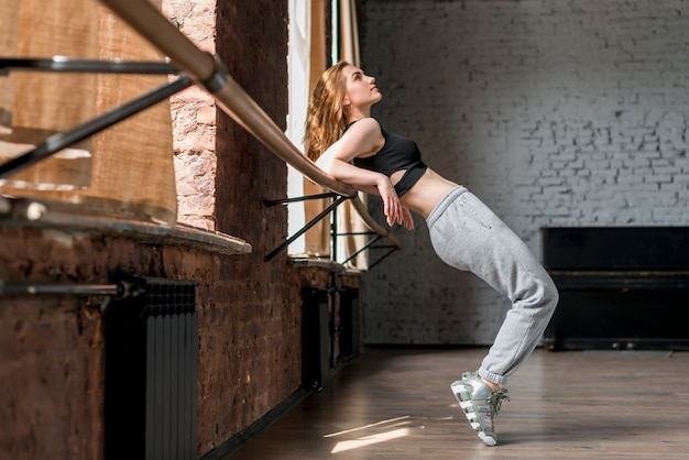 Young woman stretching on barre in the studio Free Photo