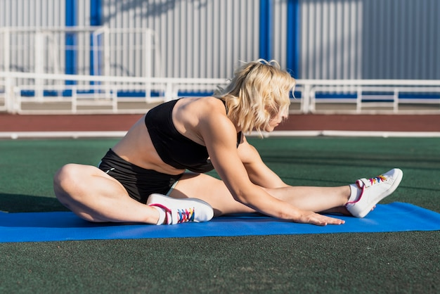 Young woman stretching on mat Free Photo