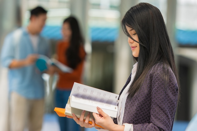 Young woman student with books in hands at campus. Premium Photo