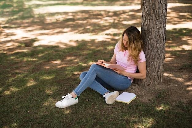 Молодая женщина учится в парке Бесплатные Фотографии